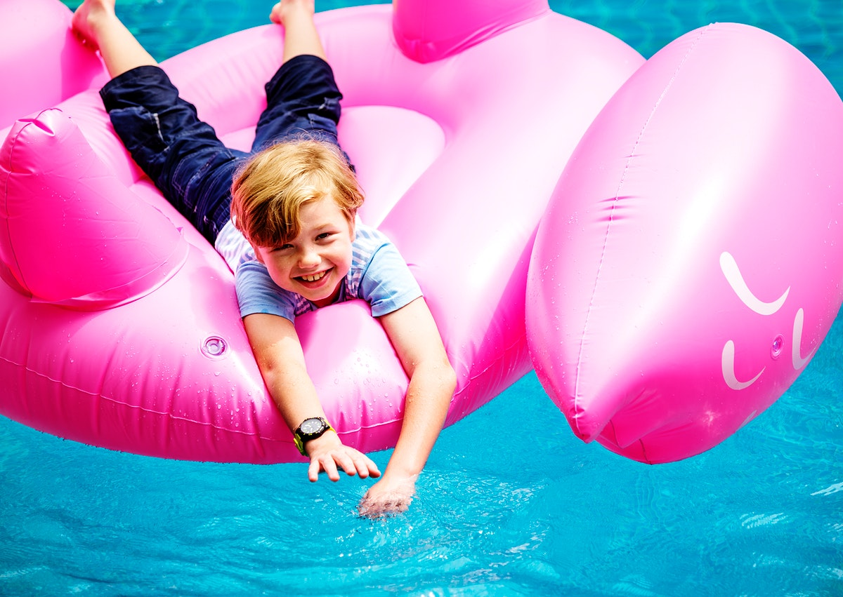 Aerial view of young caucasain boy floating in the pool with flamingo shape inflatable tube