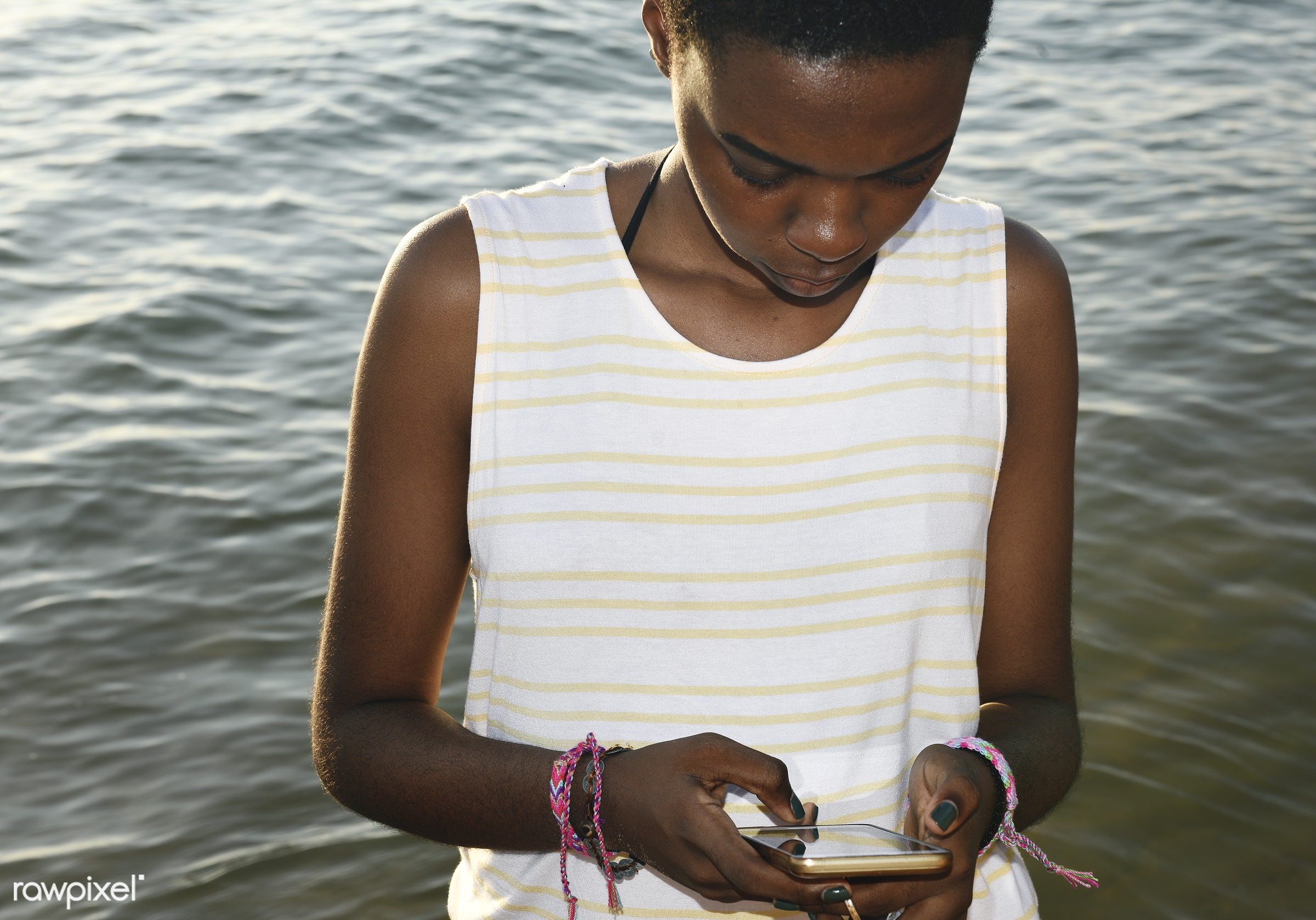 African descent woman using mobile phone by the sea - using, african descent, sea, beach, coast, female, woman, outdoors,...