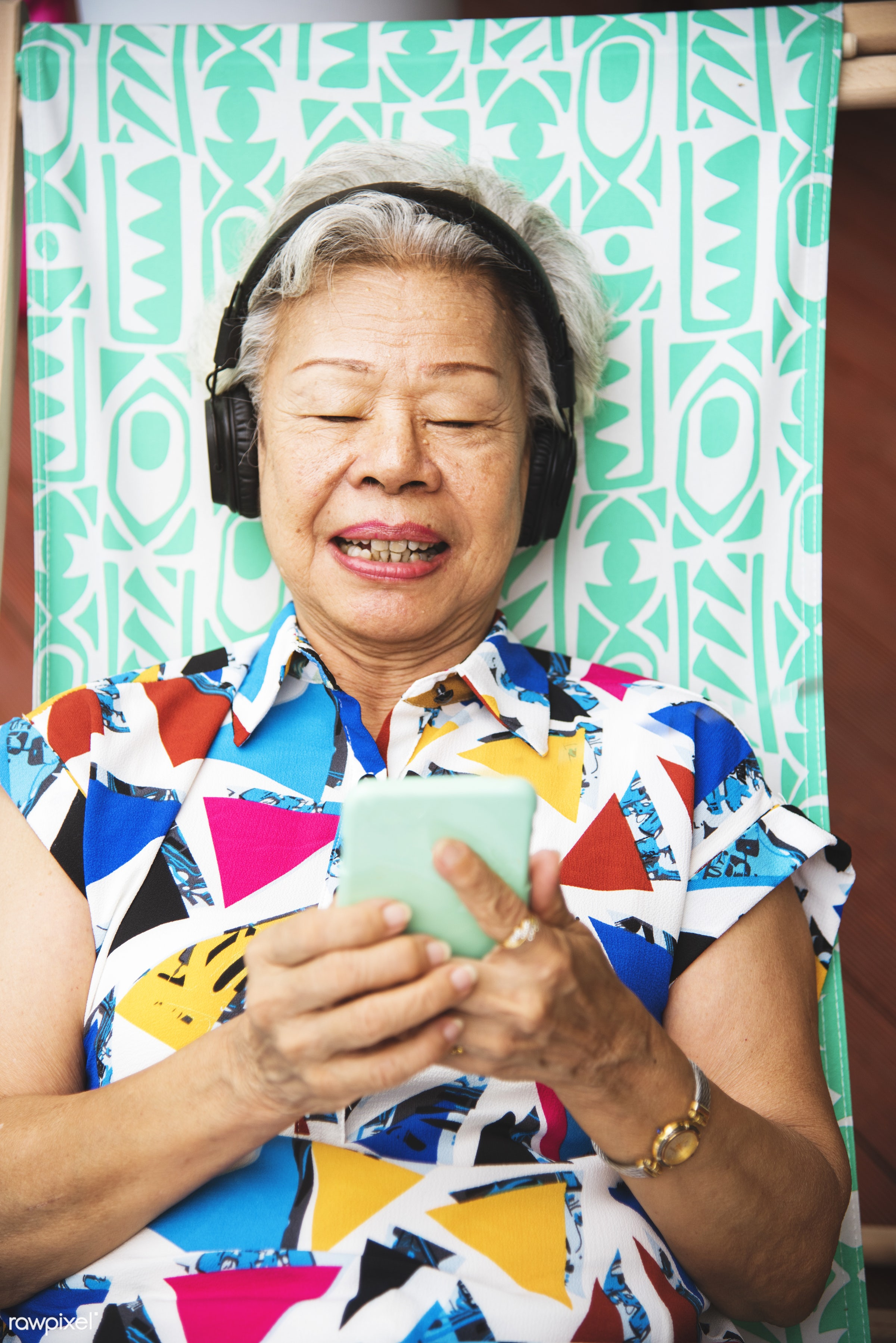 technology, asian ethnicity, casual, mobile phone, cheerful, smiling, music, leisure, adult, deck chair, headphones, lay...