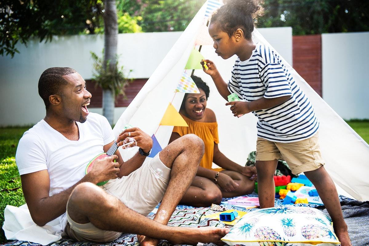 Black family enjoying summer together at backyard blowing soap bubbles