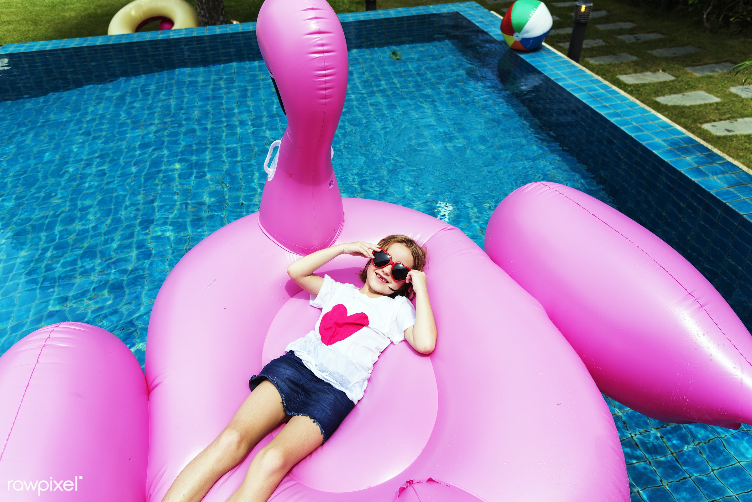 Aerial view of young caucasian girl floating in the pool with flamingo shape inflatable tube - aerial view, alone, cheerful...