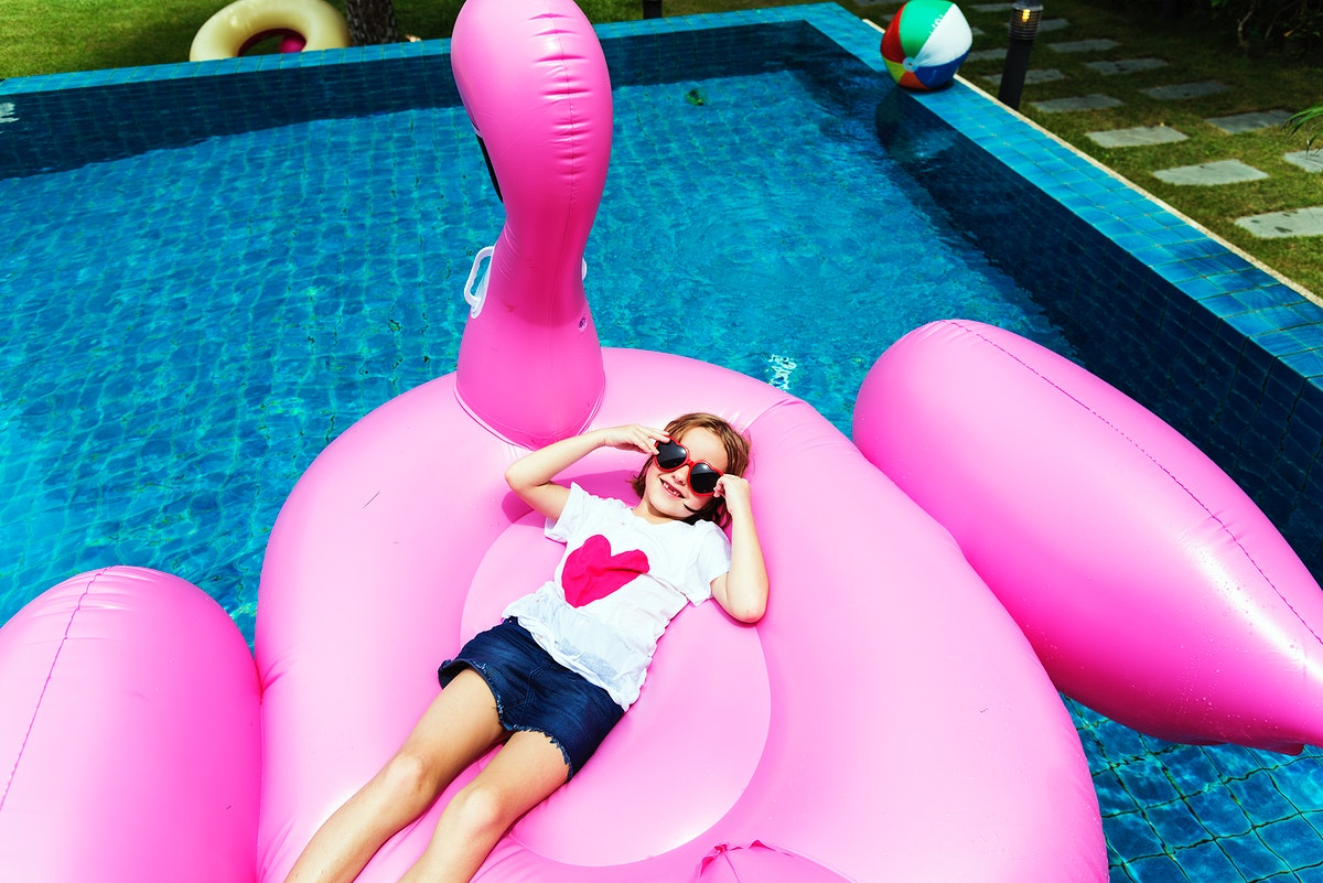 Aerial view of young caucasian girl floating in the pool with flamingo shape inflatable tube