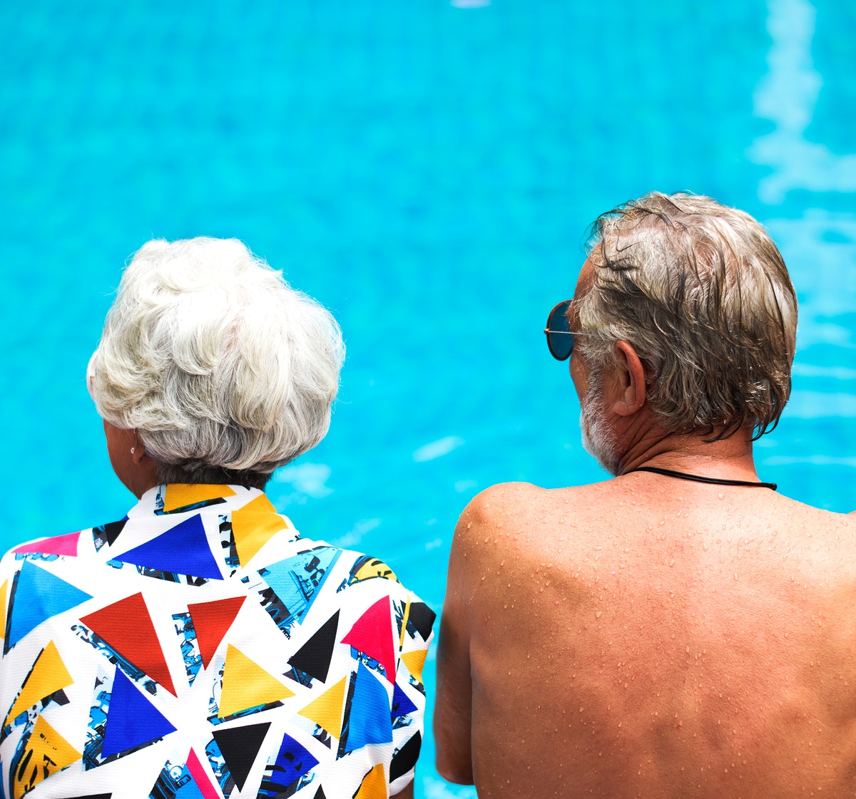Senior couple sitting by the pool