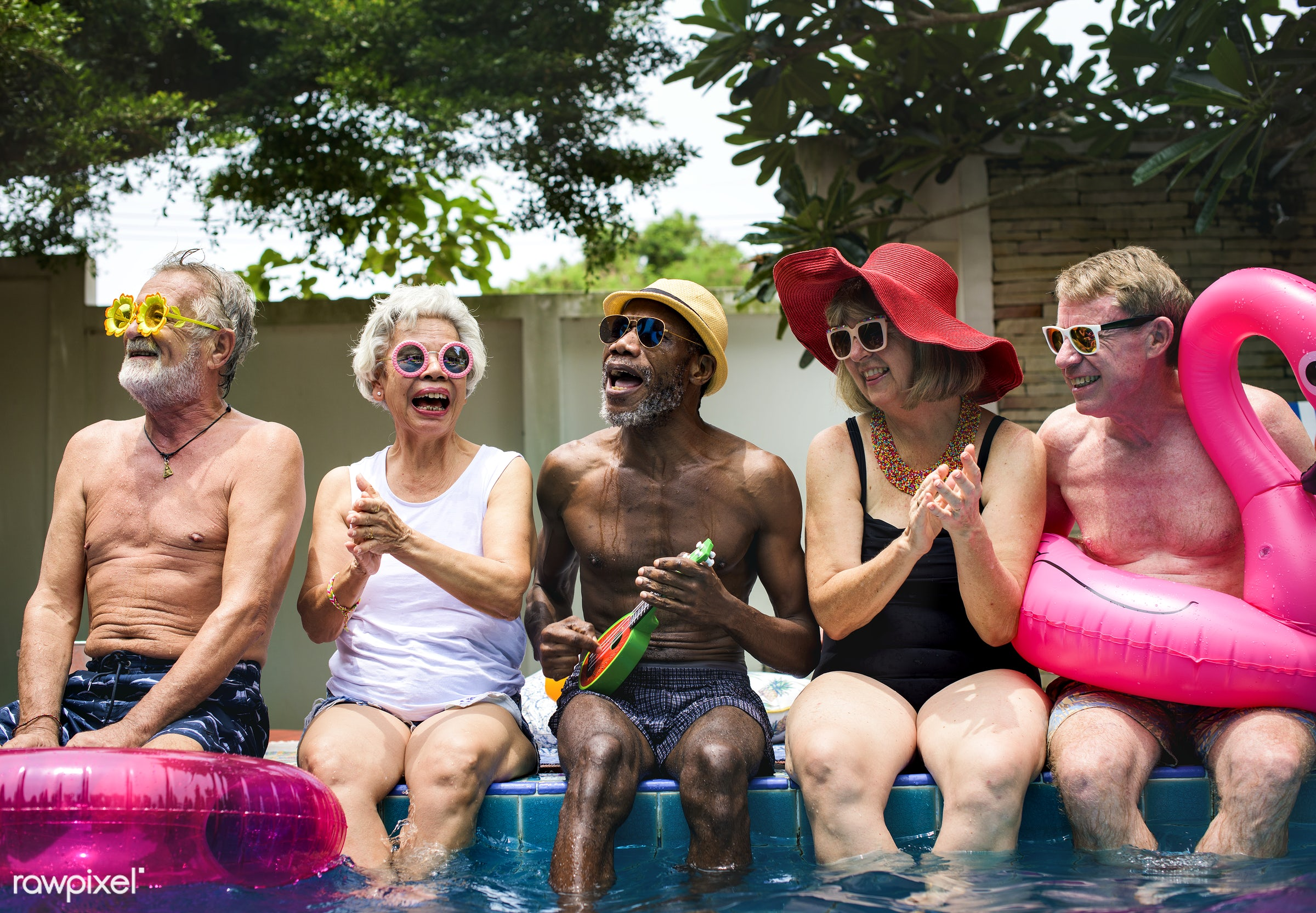 Group of diverse senior adults sitting by the pool enjoying summer together - closeup, diverse, family, friends, gathering,...