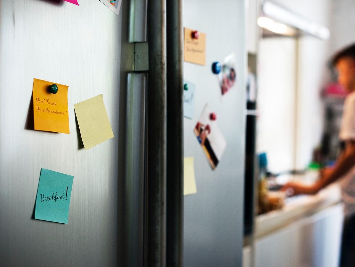 Closeup of notes on fridge doors in kitchen