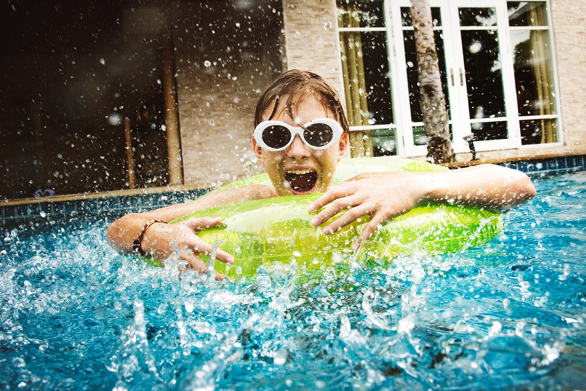 Young caucasian boy enjoying floating in the pool with tube