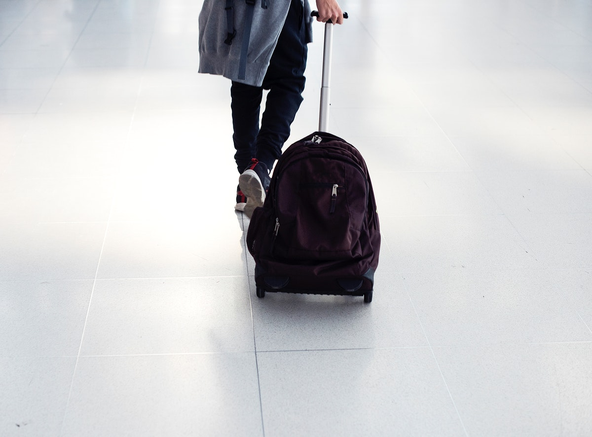 Young caucasian boy travel with luggage in the airport