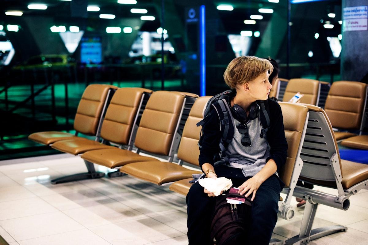 Young caucasian man sitting waiting at airport