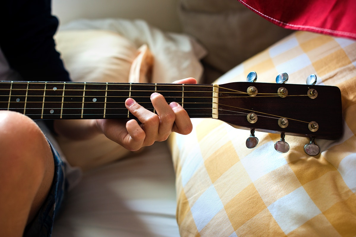 Closeup of young caucasian boy playing guitar on bed