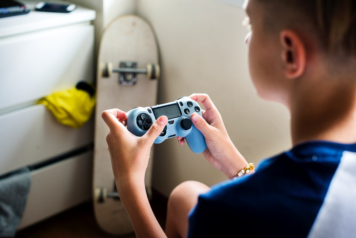 Young caucasian boy holding game control sitting on bed