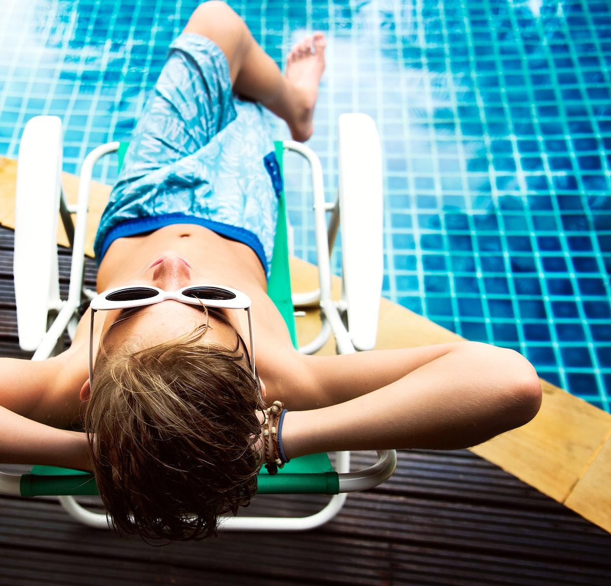 Young caucasian boy enjoying sunbathing by the pool
