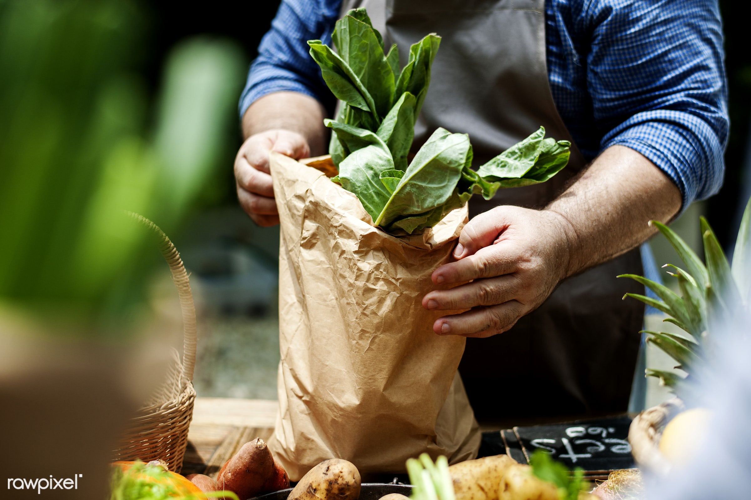 A seller putting vegetable in a bag - raw, diverse, farm, ingredients, farmer, nature, fresh, hands, products, closeup,...