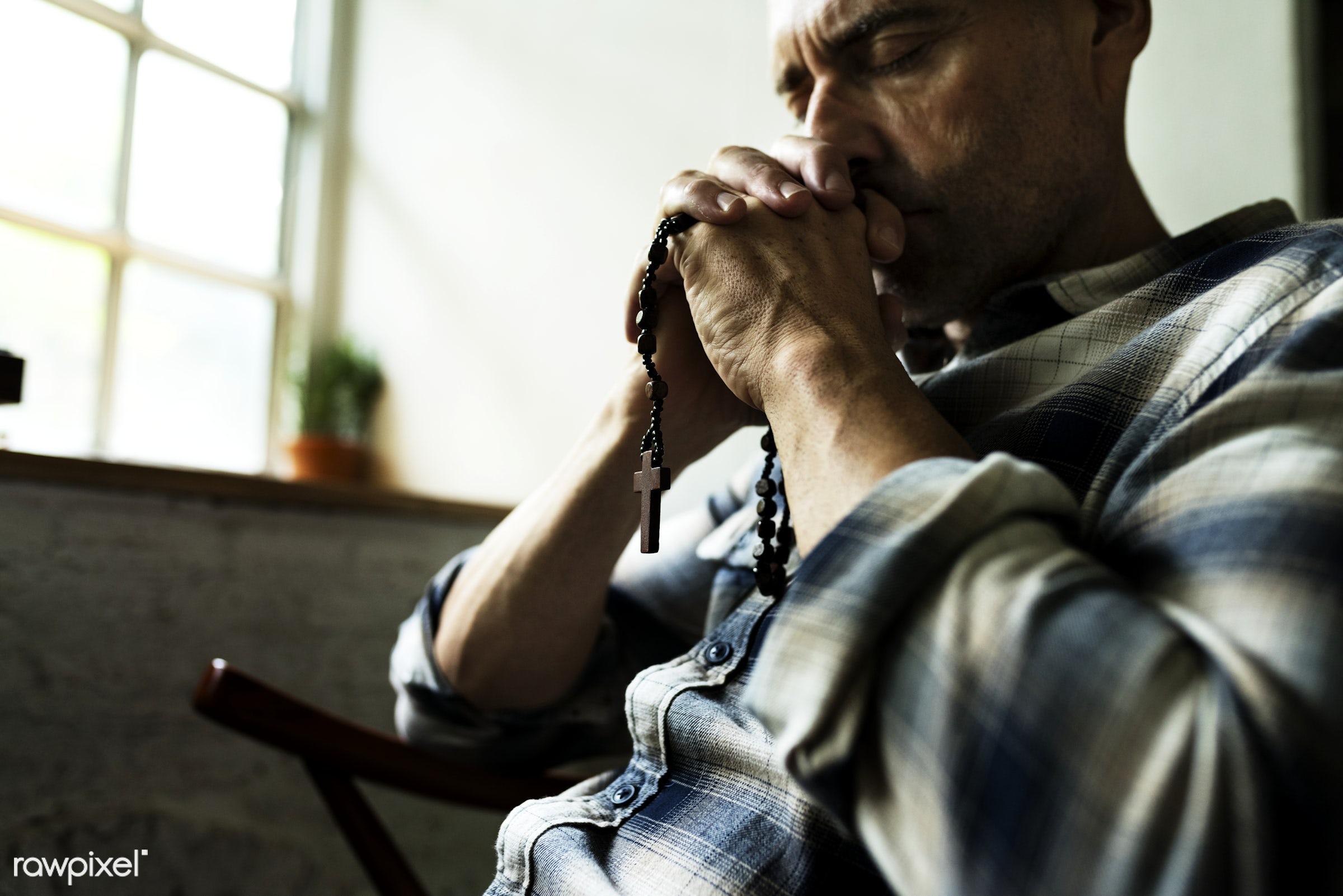 Elderly man sitting thoughtful praying - christian, god, holding, holy, believe, religion, spiritual, hands, pray, closeup,...