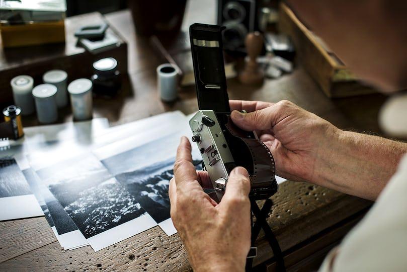 Closeup of senior man using retro classic film camera