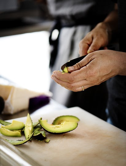 Closeup of hands peeling avocado
