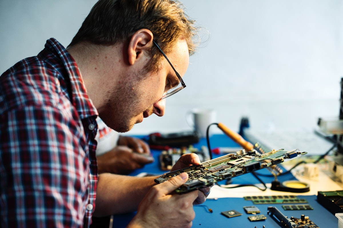 Side view of technician working on computer mainboard