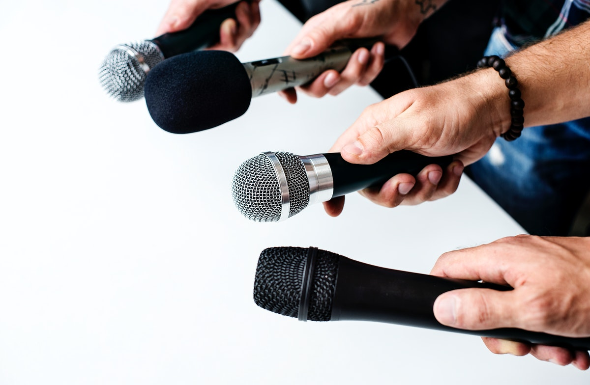 Hands holding microphone point to the same direction