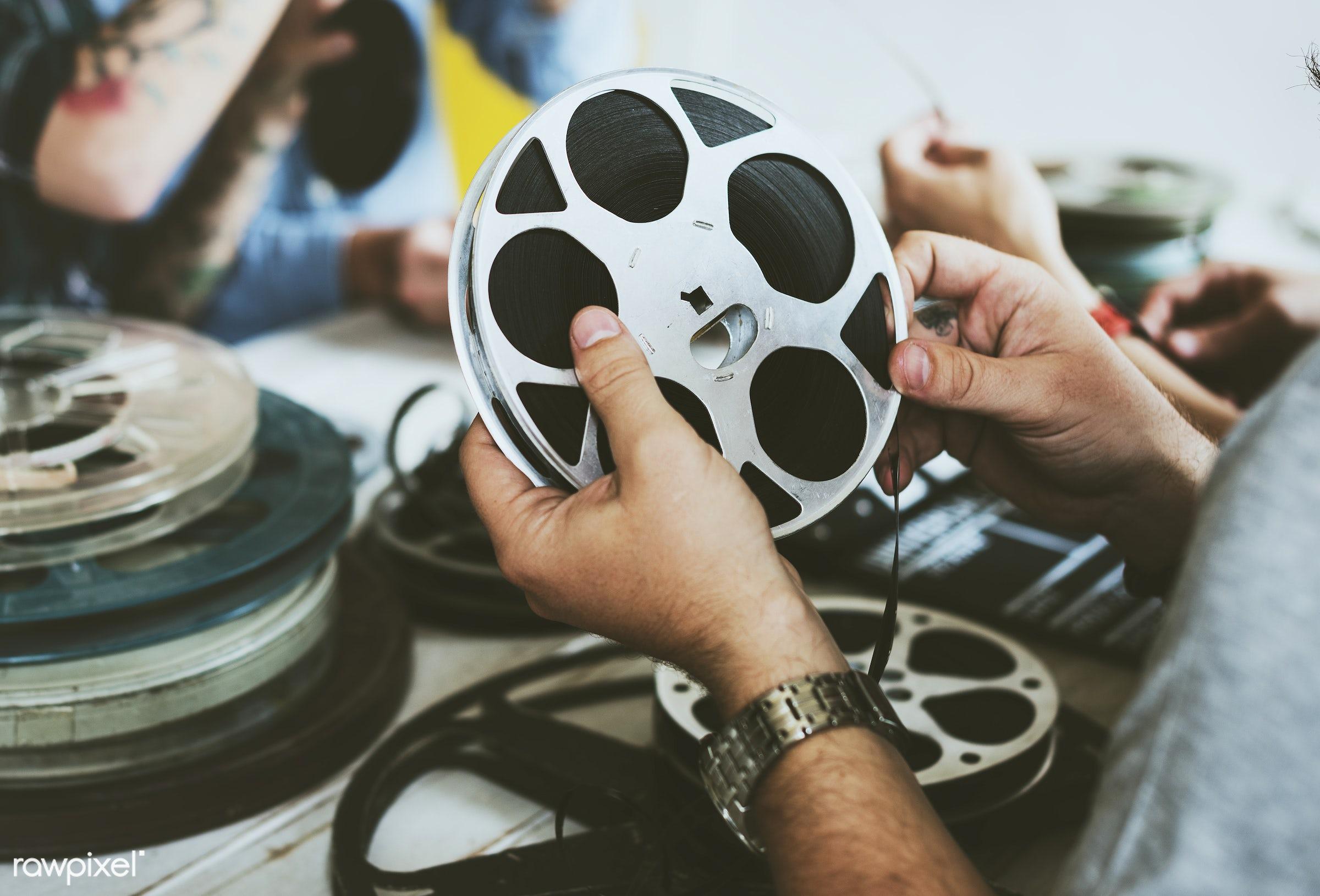 Hand hold a film strip - action, analog, antique, cinema, entertainment, equipment, film, film strip, hands, holding, movie...