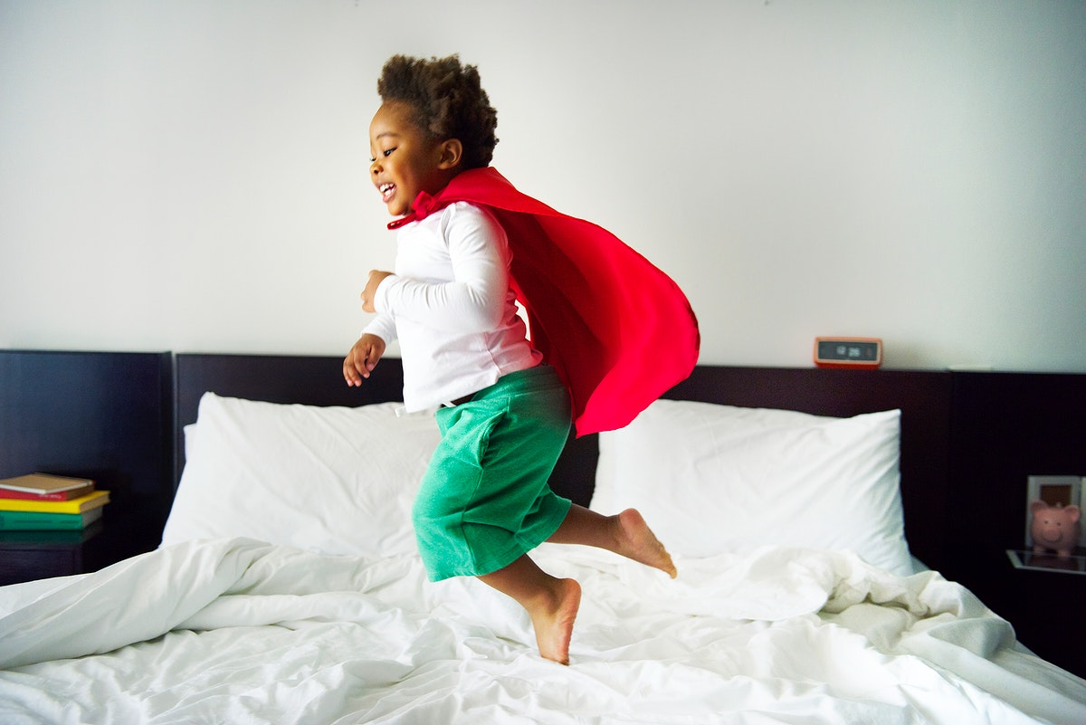 African descent kid jumping on the bed with robe