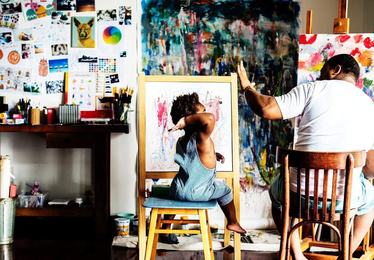 African descent artist dad giving his child a high five