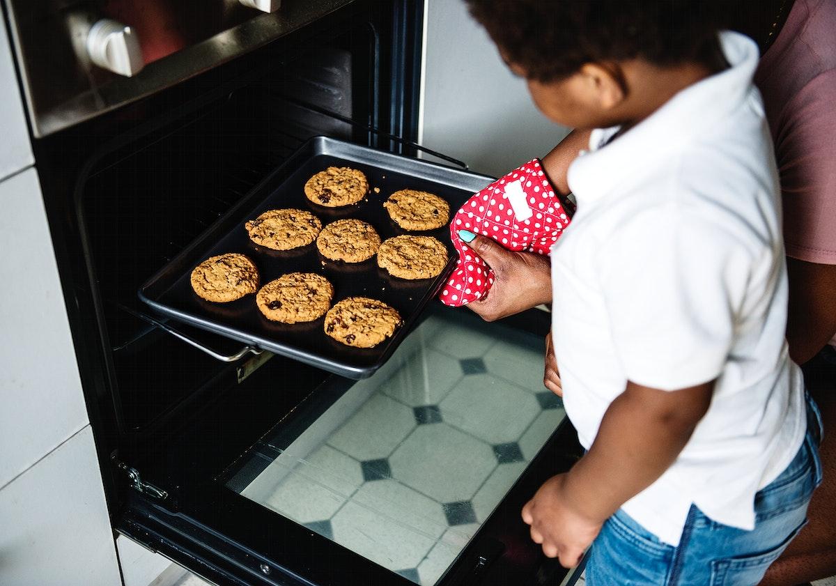 Black kid helping mom baking cookies