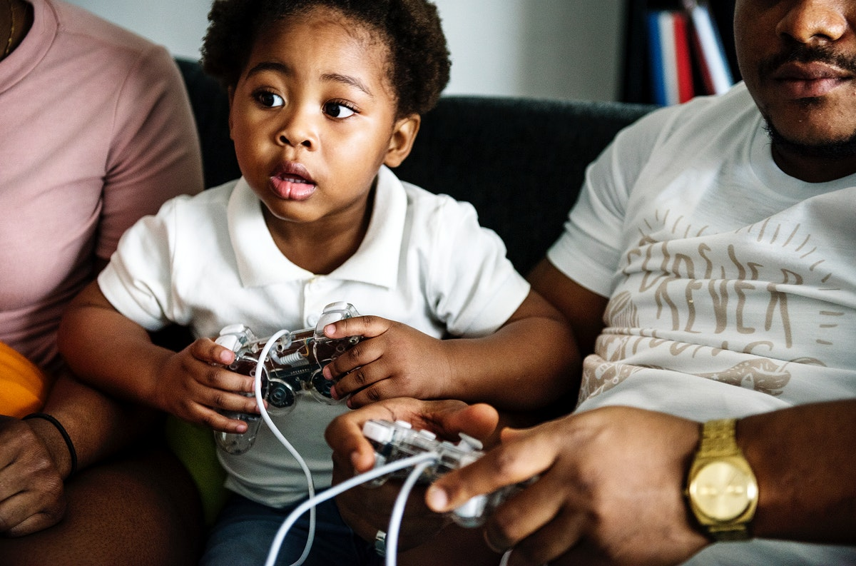 Black family playing game console together