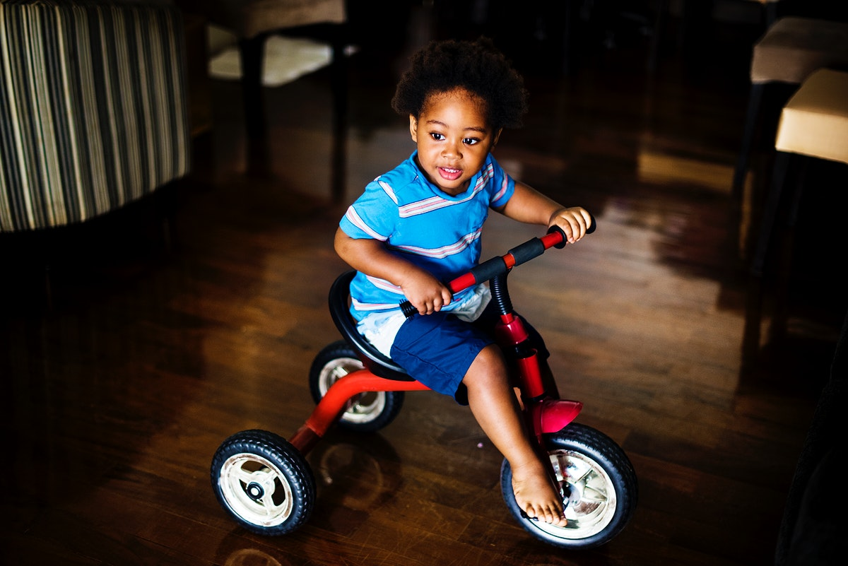 Black kid riding the bike in the house