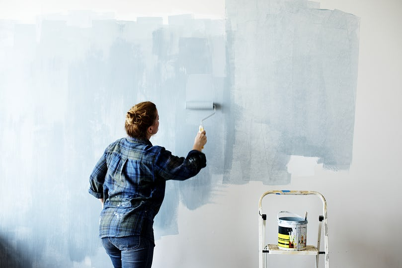Construction woman painting the wall