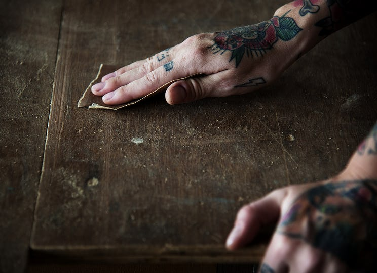 Hands with tattoo using sandpaper on a wood