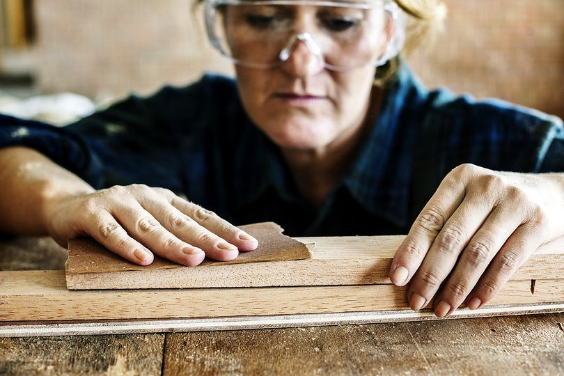 Woman carpenter using sandpaper on a wood
