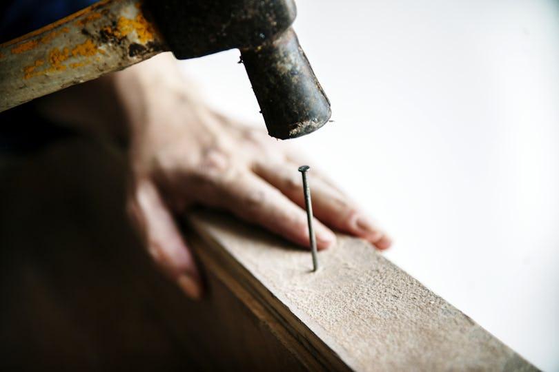 Woman carpenter using hammer pushing nail on a wood