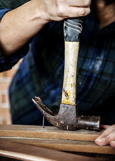 Canpenter using hammer pull a nail out from a wood