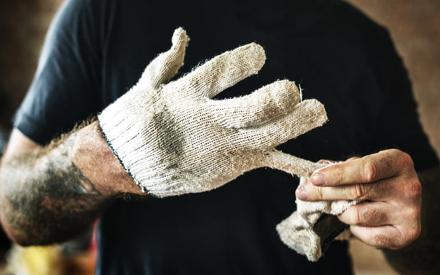 Handyman with tattoo pulling out a glove