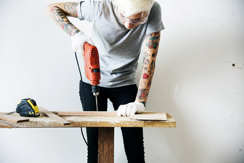 A carpenter using a drill on a wood