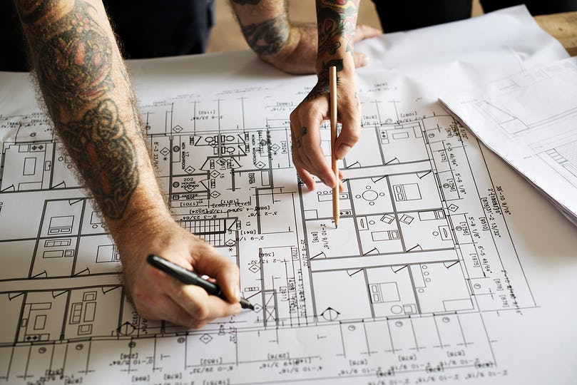 Hands with tattoo planning on a blueprint