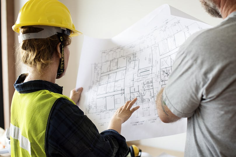 Construction team and blueprint on site