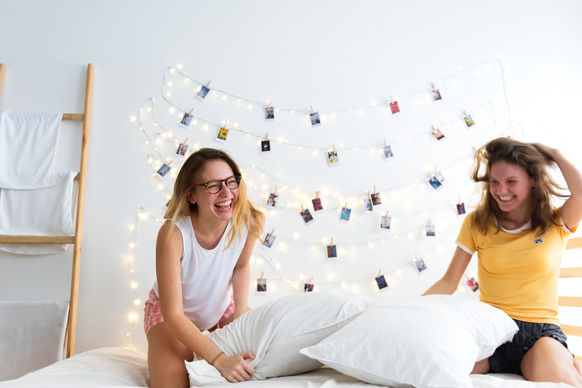 Women playing pillows fight on bed together