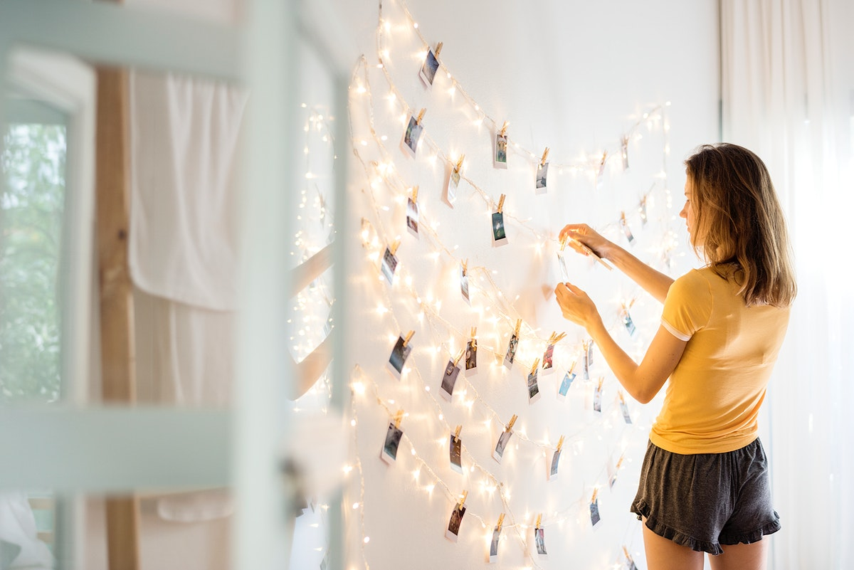 A young woman looking at photos hanging on decoration lights