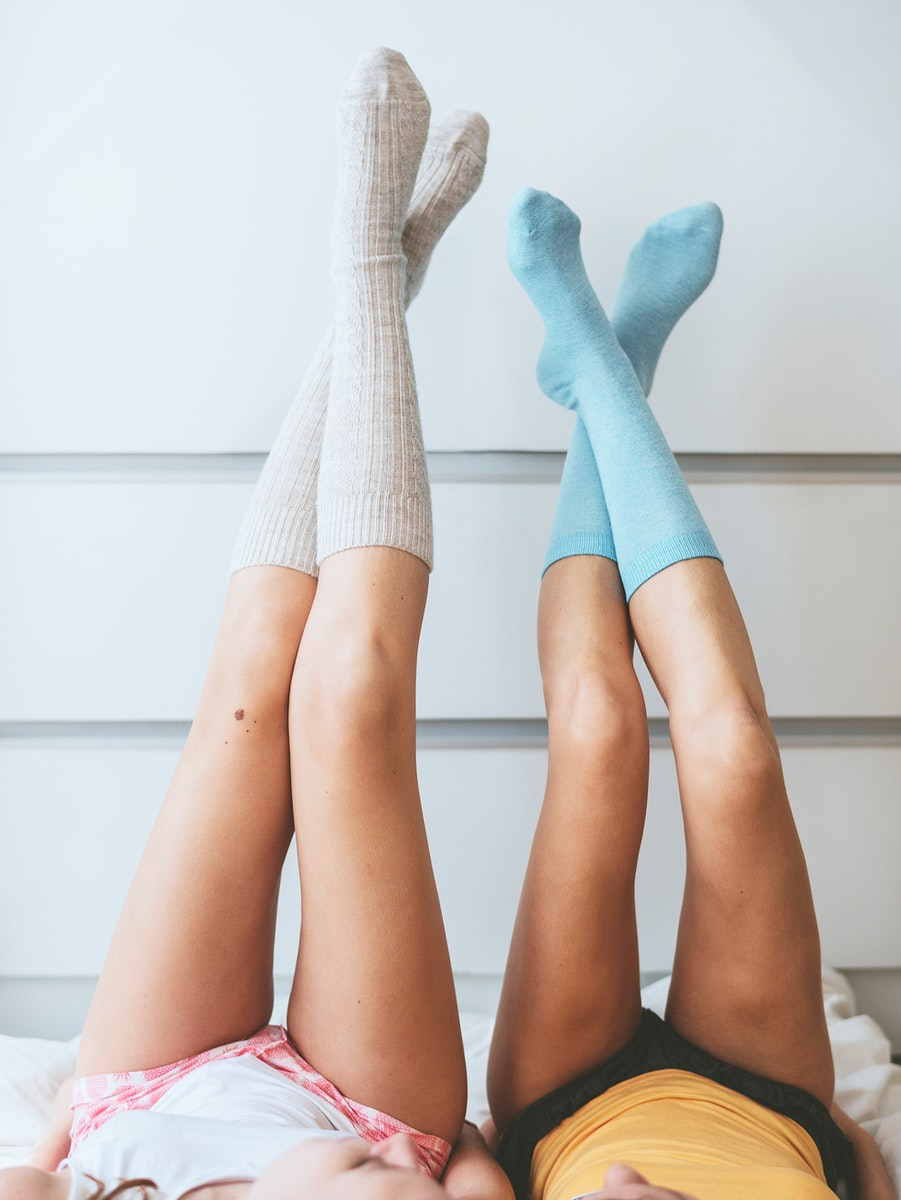 Women with their legs against the wall