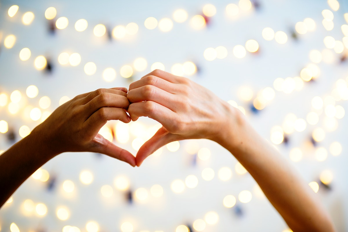 Heart shaped hands with decoration lights as a background