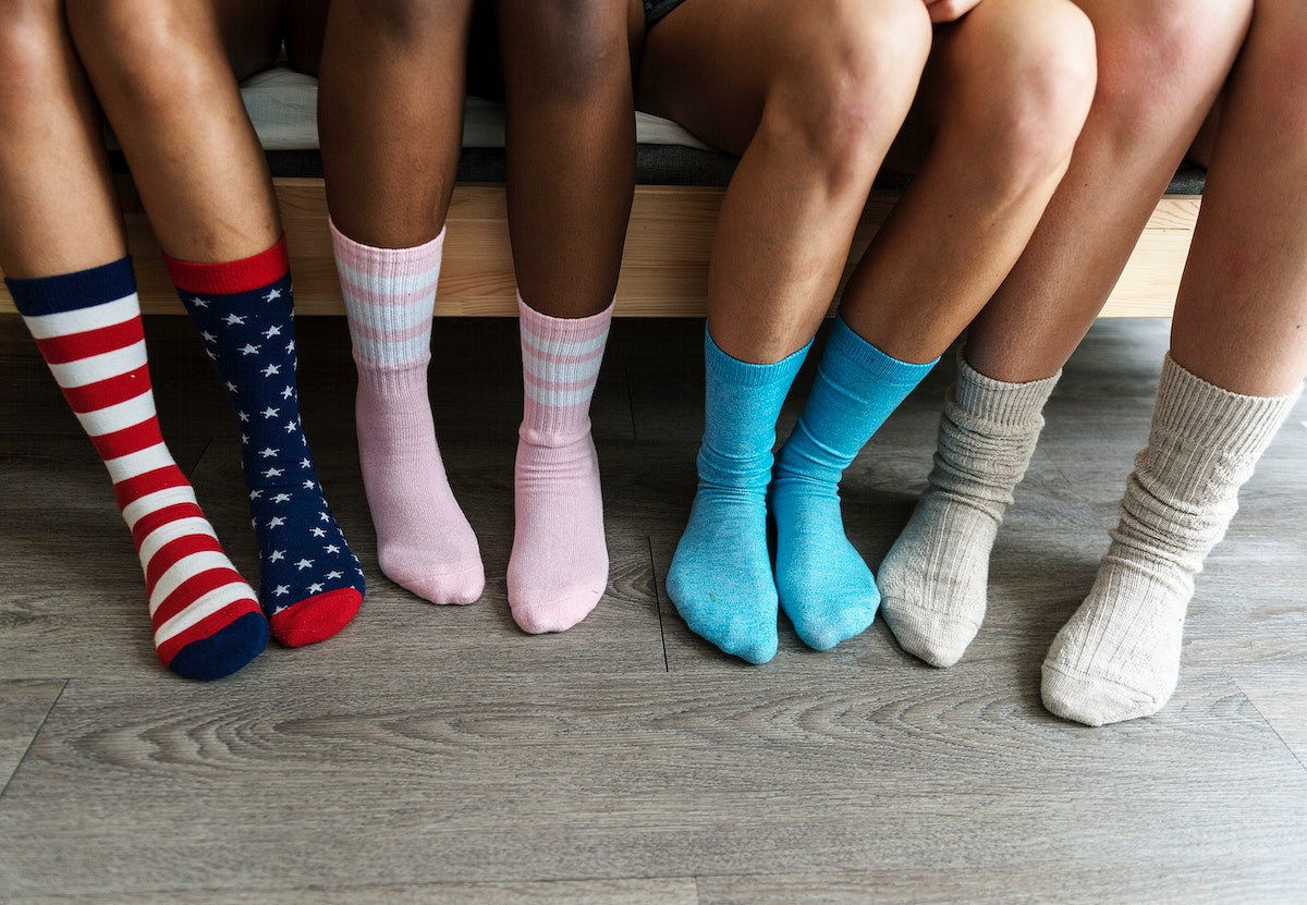 Closeup of four pairs of legs with socks