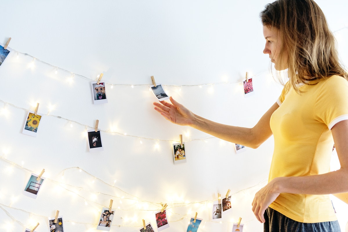 Woman looking at photos hanging with decoration lights on the white wall