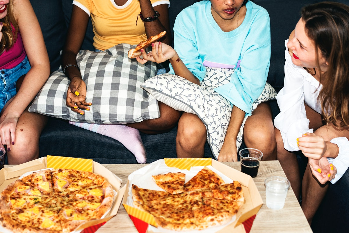 A group of diverse women sitting on the couch and eating pizza together