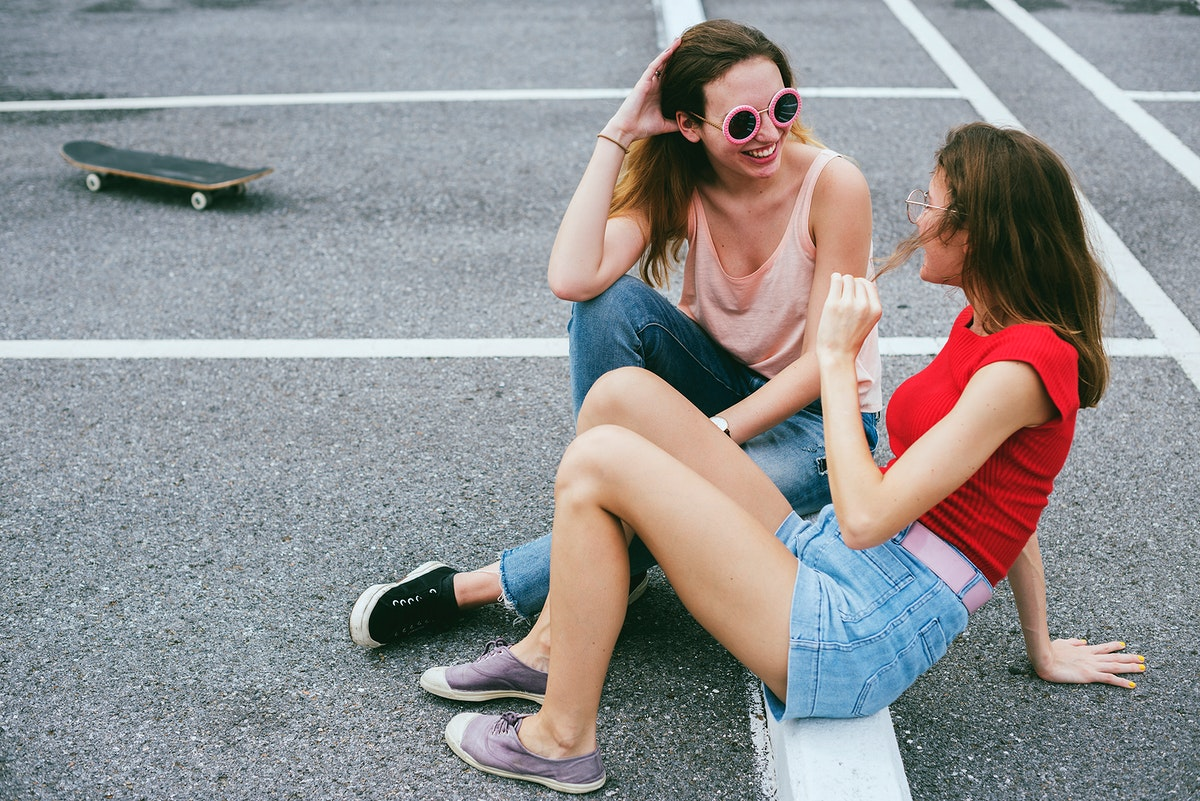 Woman friends sitting on the ground and talking together