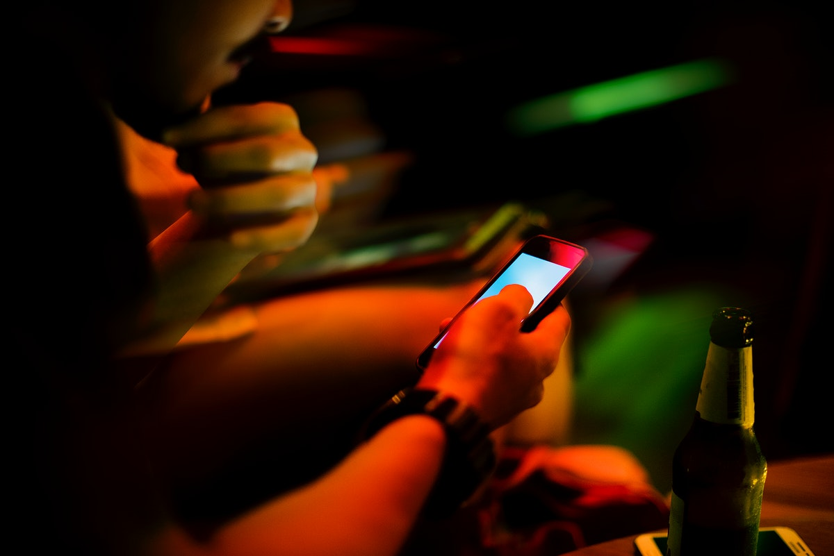 Closeup of people using mobile phone night time