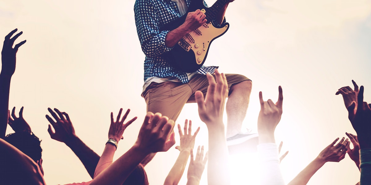 Closeup of diverse arms raised in live music concert