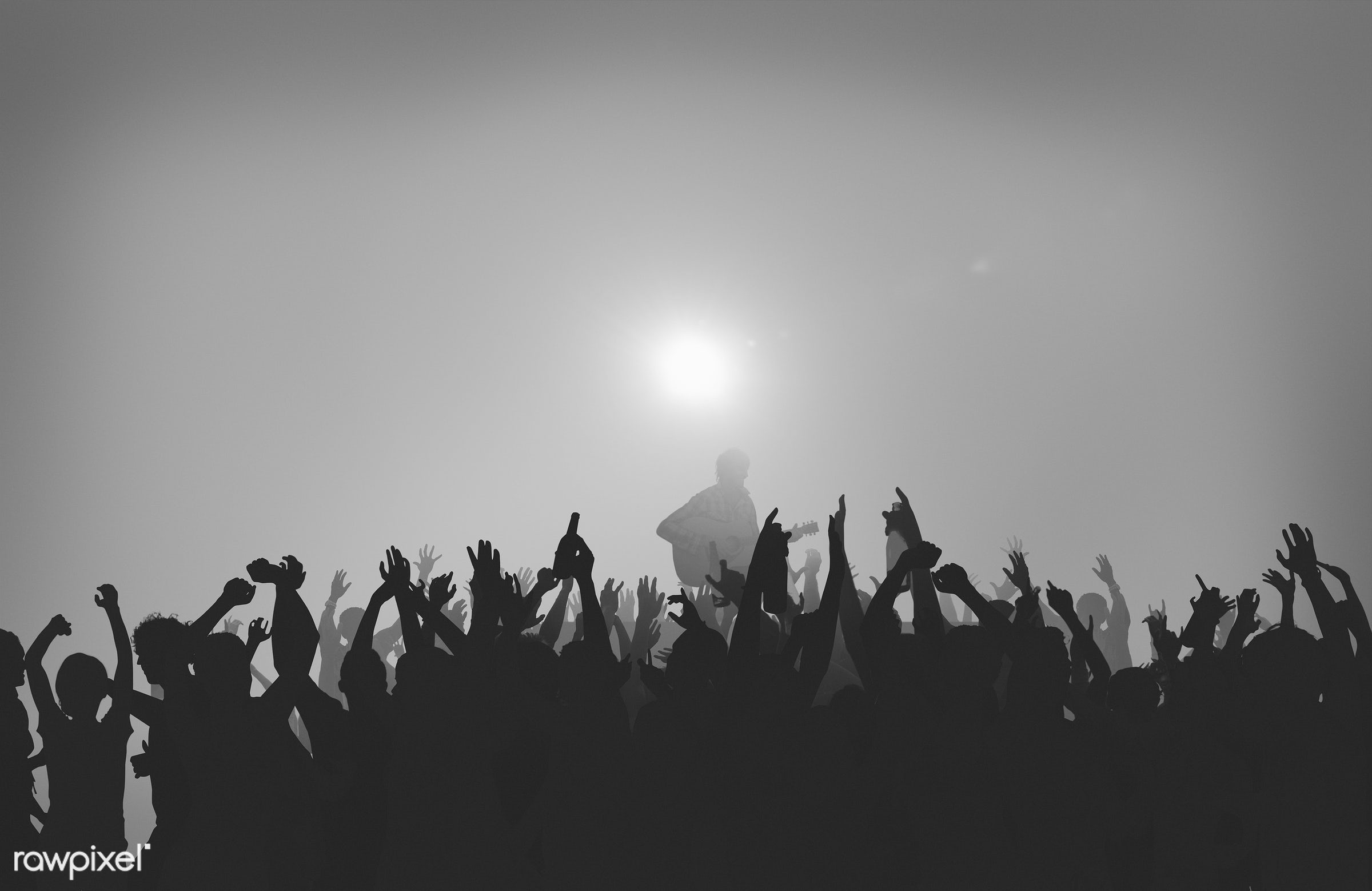 Silhouette of a crowd at an outdoor festival - adolescence, arms raised, audience, back lit, carefree, celebration, cheerful...