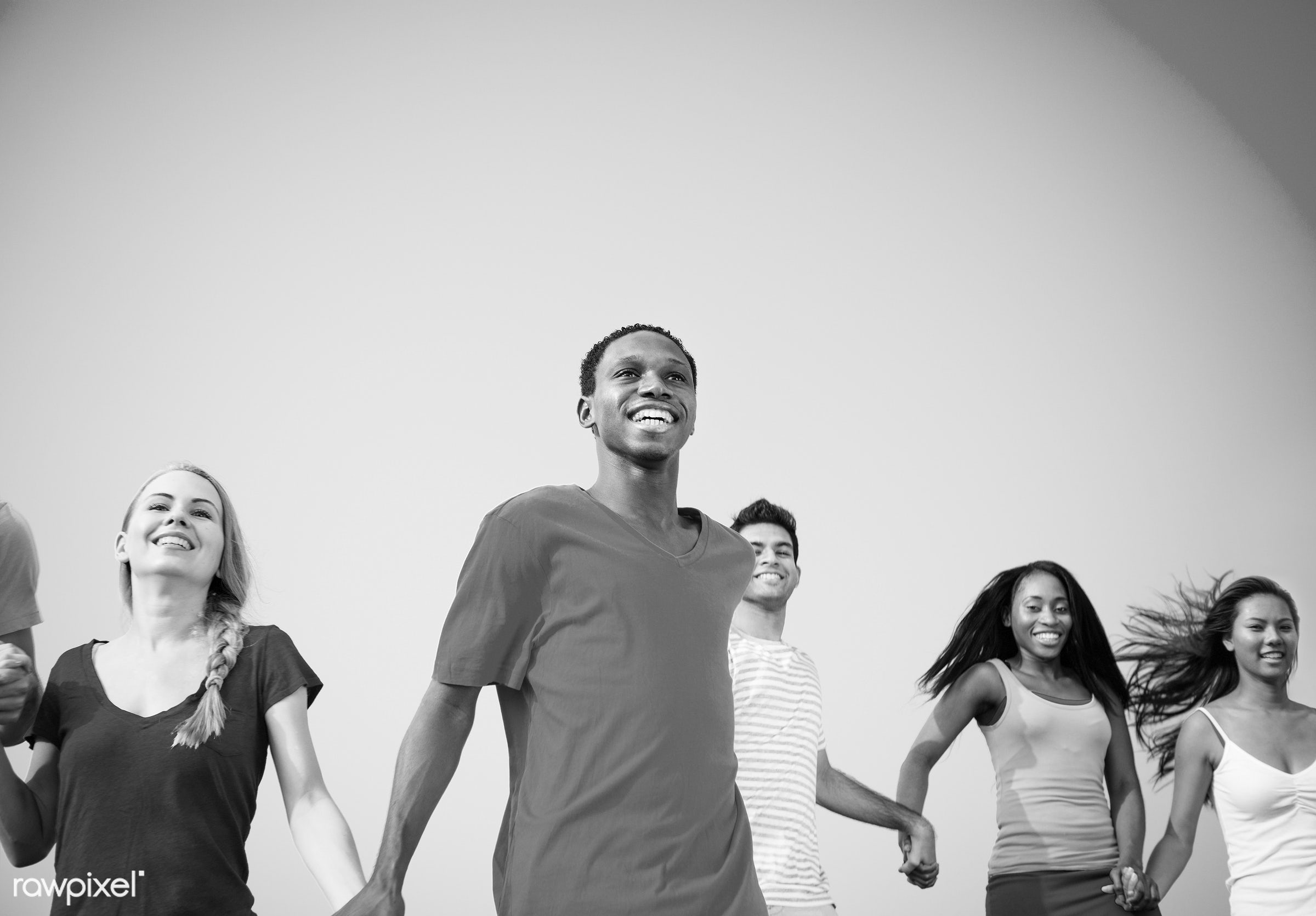 Diverse young people running while holding each other's hands - african, black, blue sky, bonding, cheerful, cloud,...