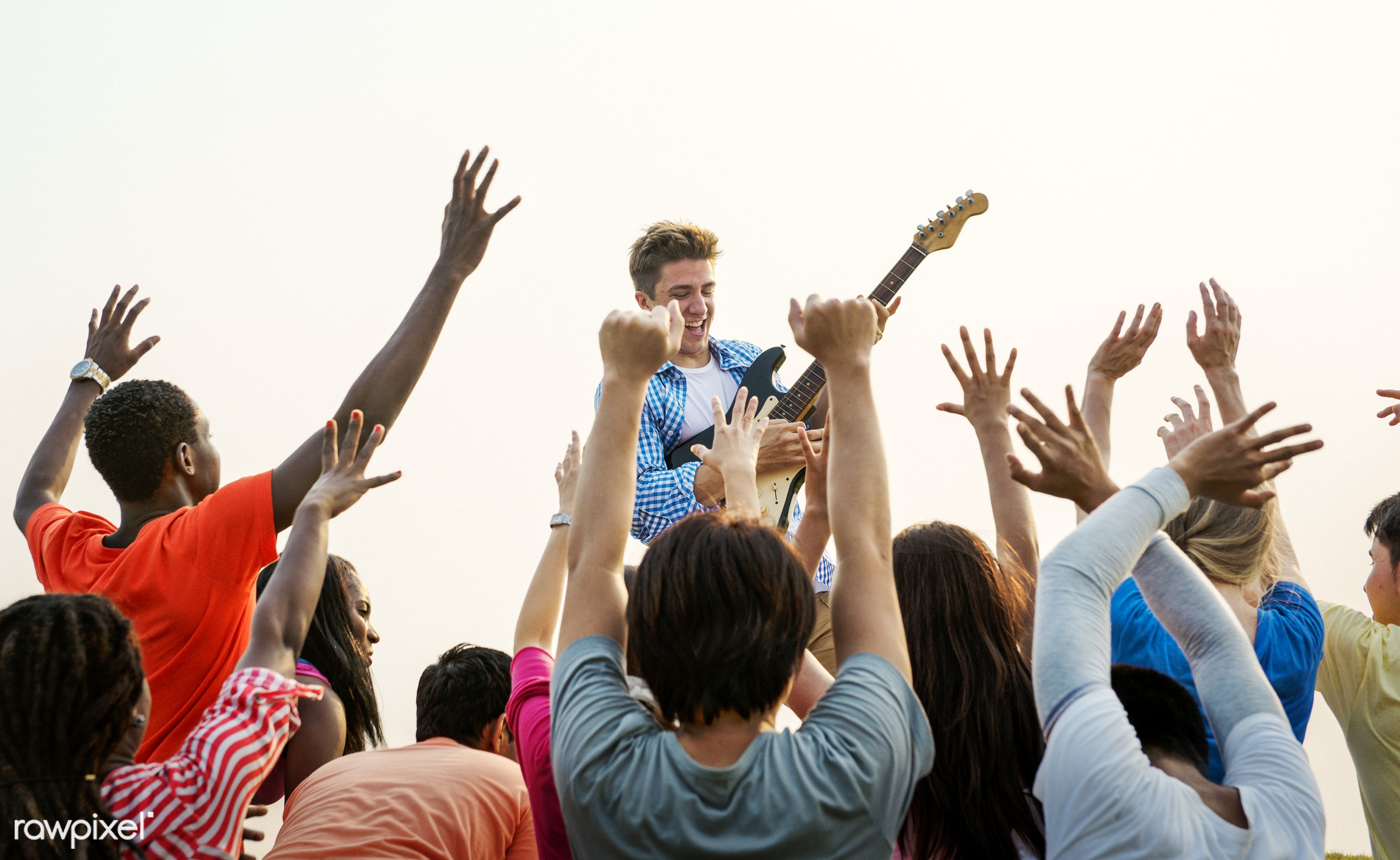 Guitarist playing at a music festival - love, rock, allies, arms raise, casual, celebration, cheerful, circle of friends,...