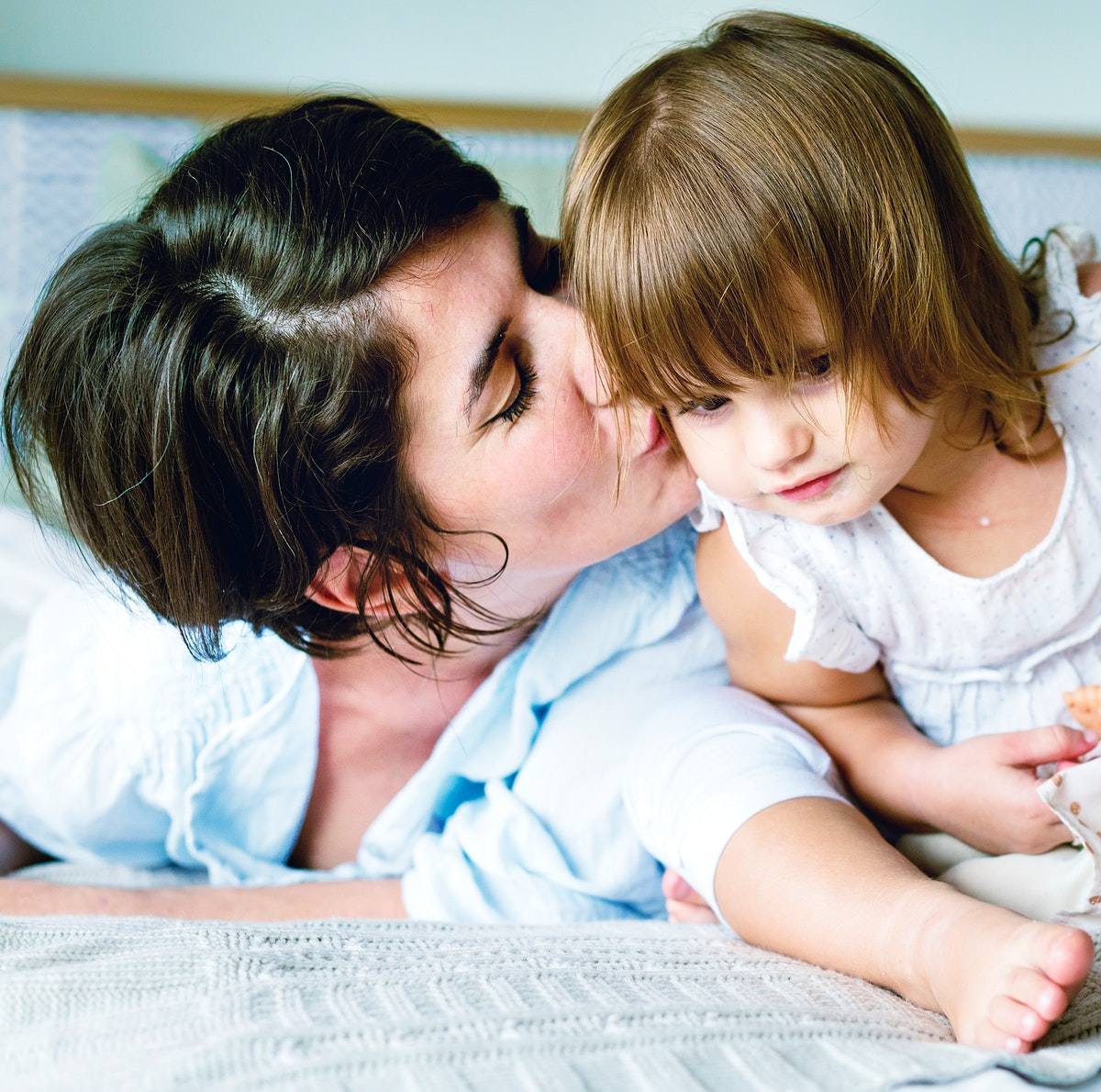 Mother kissing daughter with love